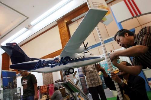 Dua orang pria sedang memperhatikan replika Pesawat Udara N219