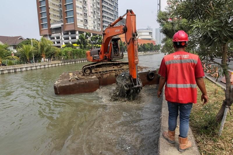 Pekerja mengawasi alat berat yang dioperasikan untuk mengeruk material endapan berupa lumpur bagian dari normalisasi Kalimalang, Bekasi, Jawa Barat, Kamis (12/7). MI/PIUS ERLANGGA.