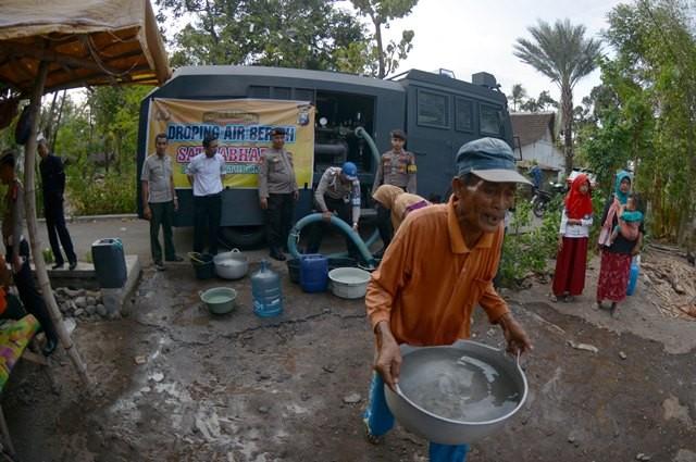Seorang warga mengambil air bersih yang dibagikan Polres Situbondo di Desa Selowogo, Bungatan, Situbondo, Jawa Timur, Senin (1/10). ANTARA FOTO/Seno.