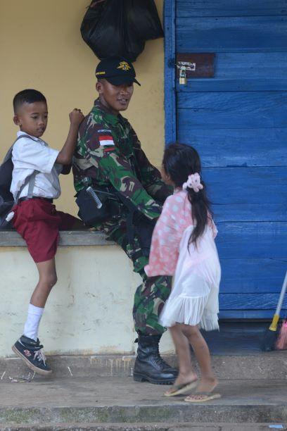 Siswa bermain dengan anggota TNI usai pulang sekolah, di Papua,