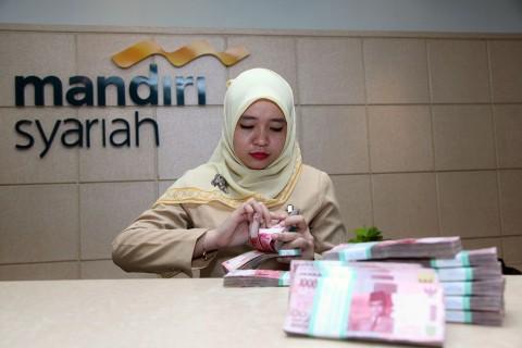 Petugas menghitung uang di Bank Syariah Mandiri, MI/Panca