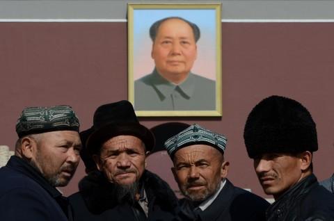 Sekelompok etnis Uighur berfoto di depan foto Mao Zedong. (Foto: