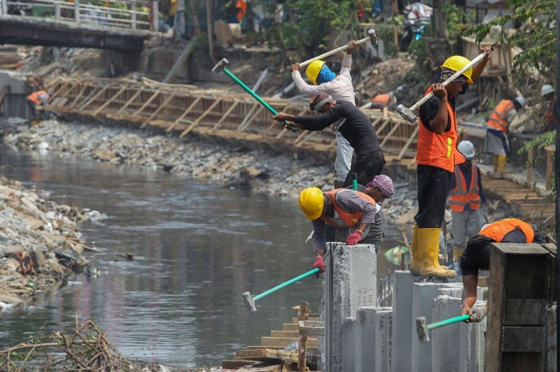 Pekerja menyelesaikan proses pemasangan turap bagian dari normalisasi sungai di sepanjang Kali Grogol, Palmerah, Jakarta Barat. (Foto: MI/Pius Erlangga)
