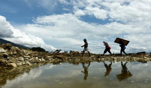 Warga mengangkat sisa-sisa bangunan yang masih bisa digunakan di lokasi terdampak pergerakan atau pencairan tanah (likuifaksi) di Balaroa Palu, Sulawesi Tengah, Minggu (14/10). ANTARA FOTO/Yusran Uccang.