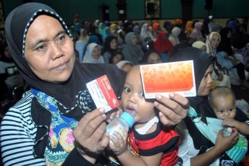 Warga menunjukkan Kartu Keluarga Sejahtera saat Penyaluran