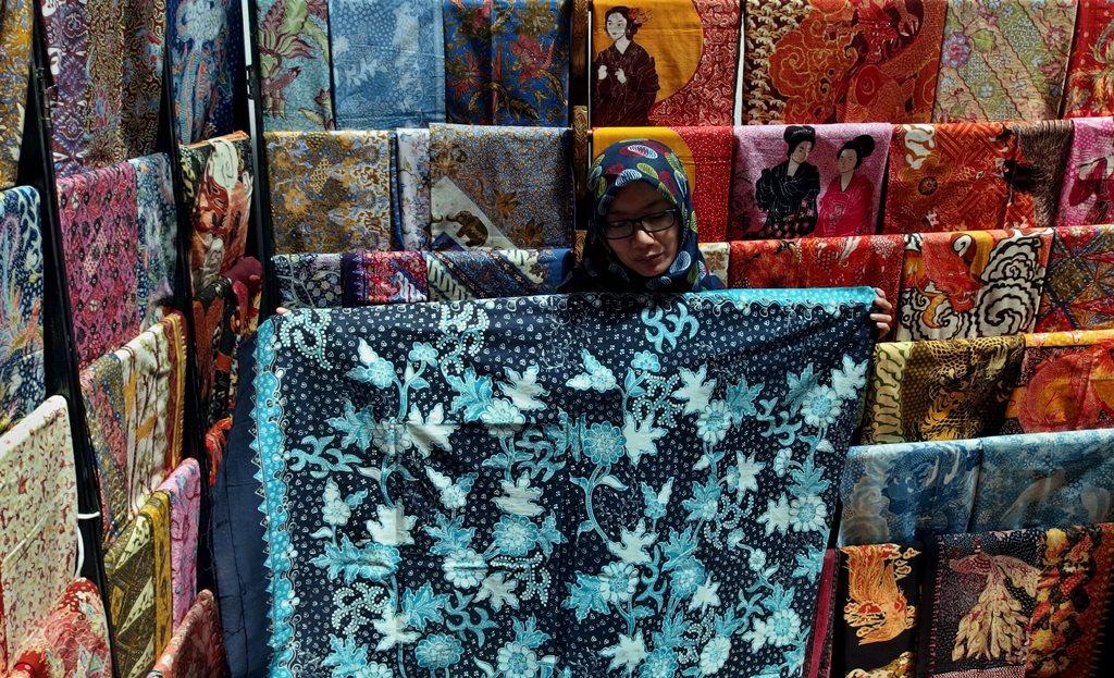 Penjaga stan memperlihatkan kain batik Lasem. (Foto: Antara/R. Rekotomo)