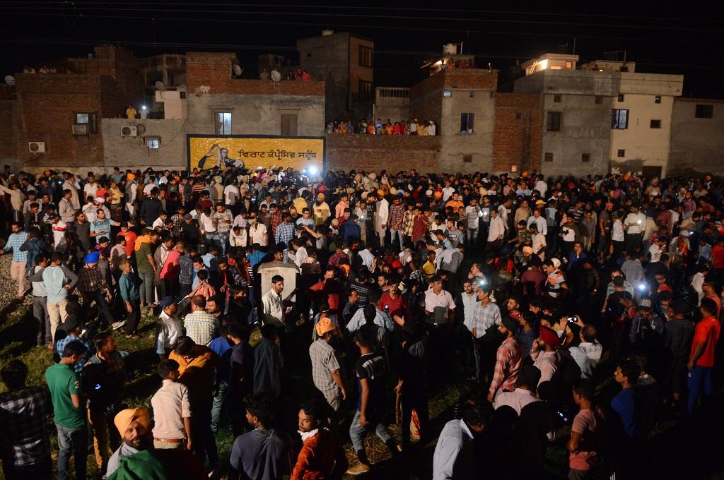 Warga berkumpul di lokasi kecelakaan kereta di Amritsar, India, 19 Oktober 2018. (Foto: AFP/NARINDER NANU)