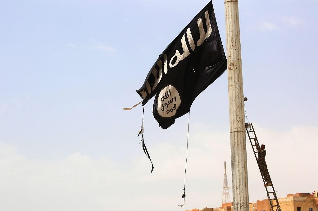 Seorang personel SDF mencoba menurunkan bendera ISIS di kota Tabqa, Suriah, 30 April 2017. (Foto: AFP/DELIL SOULEIMAN)