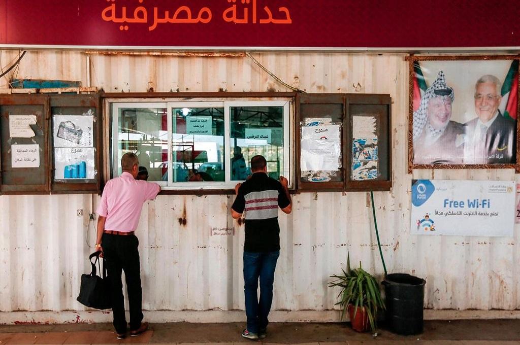 Warga menyerahkan dokumen perjalanan di perlintasan Erez. (Foto: AFP)