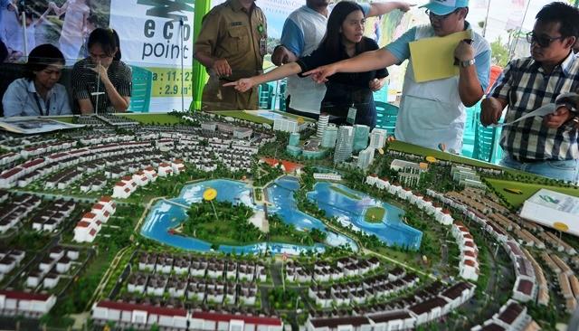 Seorang wiraniaga menjelaskan proyek perumahan mewah yang sedang dibangun di Palembang kepada seorang calon pembeli dalam sebuah pameran di sela Asian Games 2018 Palembang. Antara Foto/Fenny Selly