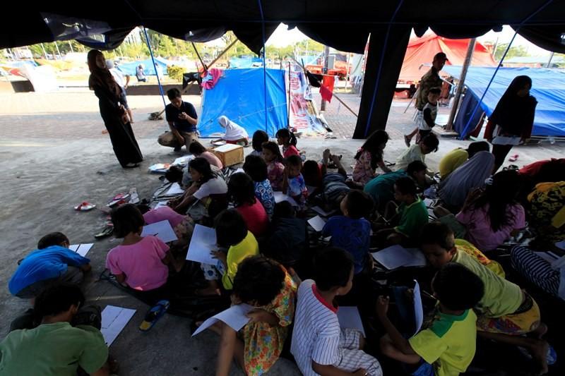 Anak pengungsi belajar di tenda darurat di pengungsian lapangan Watulemo, kantor Walikota Palu, Selawesi Tengah, Senin (8/10). MI/RAMDANI.