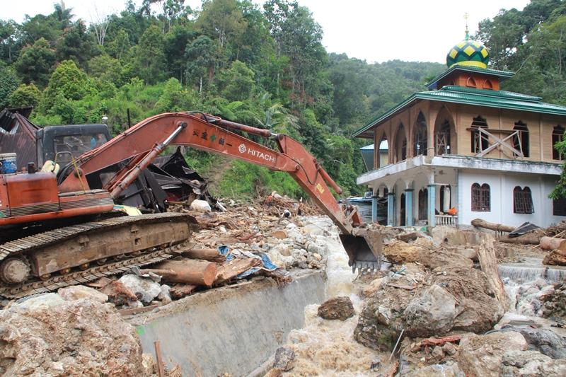 Petugas menggunakan alat berat berusaha menggeser batu yang terbawa arus sungai pascabanjir bandang yang terjadi, di Desa Muara Saladi, Kecamatan Ulu Pungkut, Mandailing Natal, Sumatera Utara, Sabtu (13/10). ANTARA FOTO/Holik Mandailing.