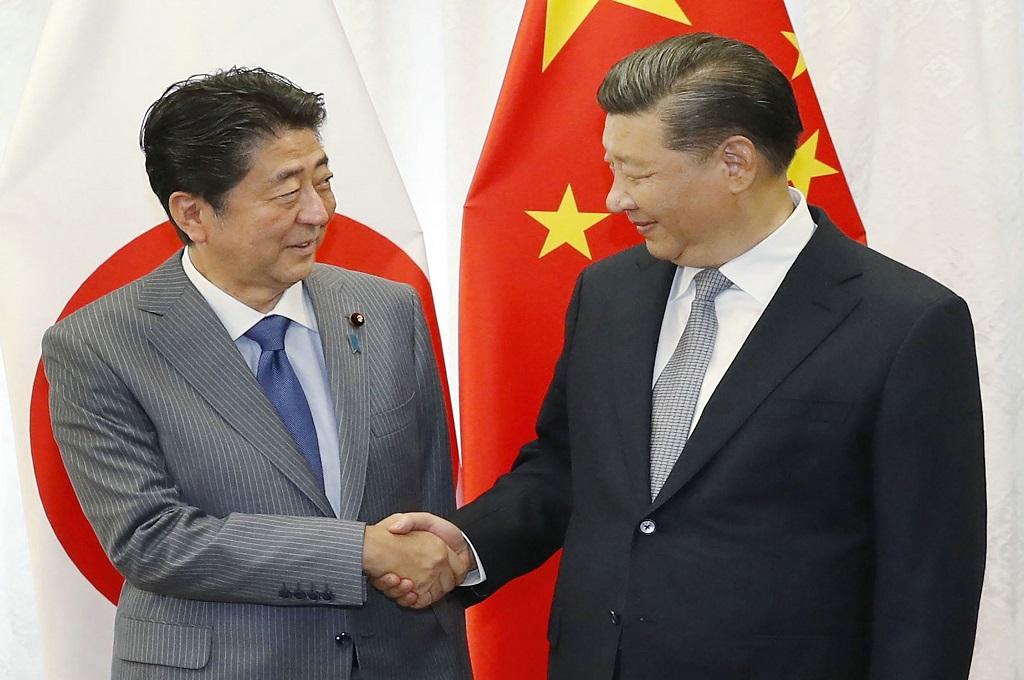 PM Jepang Shinzo Abe (kiri) berjabat tangan dengan Presiden Tiongkok Xi Jinping di Vladivostok, Rusia, 12 September 2018. (Foto: AFP/JIJI PRESS)