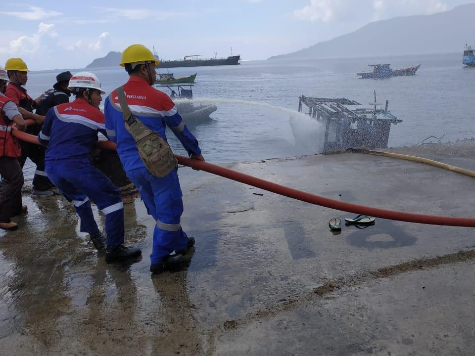 Petugas berupaya memadamkan api yang membakar kapal KM Kamarul Huda di  Pelabuhan Pertamina Selat Lampa, Kecamatan Pulau 3 Barat, Kabupaten Natuna, Selasa, 23 Oktober 2018. Medcom.id/Anwar Sadat Guna