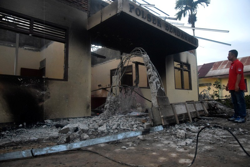 Seorang warga mengamati bangunan Polsek Bendahara yang dibakar oleh warga di Aceh Tamiang, Aceh, Selasa (23/10/2018). ANTARA FOTO/Zamzami.