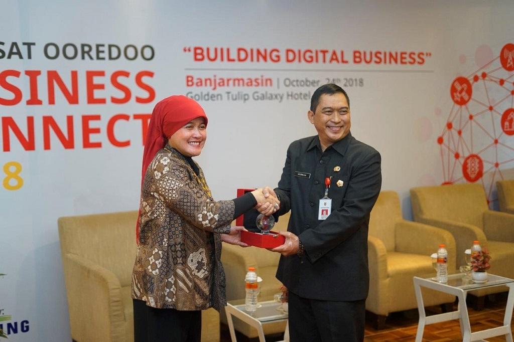 Group Head Regional Account Indosat Ooredoo, Fuli Humairoh (kiri) berjabat tangan dengan Asisten Bidang Perekonomian dan Pembangunan Sekretariat Daerah Provinsi Kalimantan Selatan, Hermansyah Manaf (kanan).