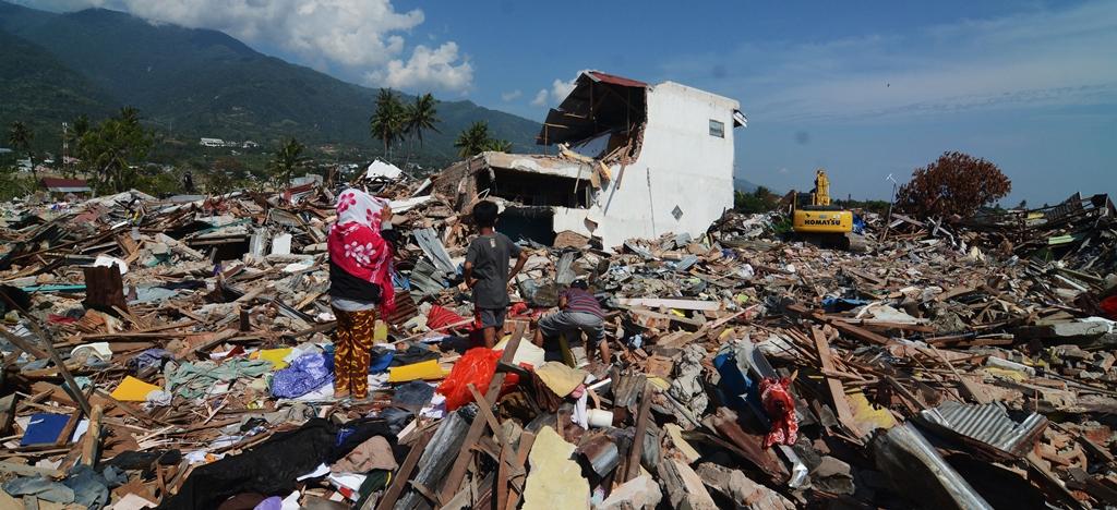 Seorang ibu bersama anaknya menyaksikan sisa-sisa reruntuhan rumahnya yang akan diratakan dengan tanah di area bekas likuifaksi di Kelurahan Balaroa, Palu. ANT/Basri Marzuki.
