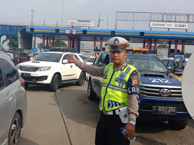 Petugas kepolisian mengatur kendaraan yang mengantre keluar dari Tol Ciawi menuju ke Puncak Bogor, Jawa Barat. Istimewa