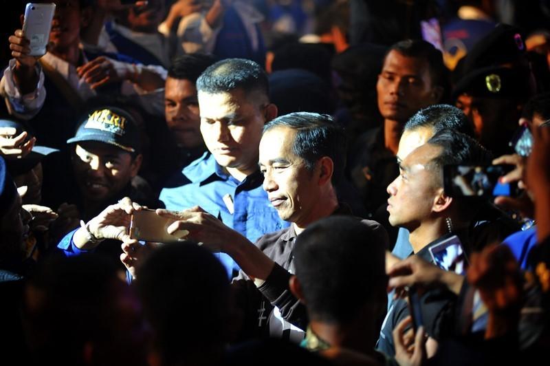 Calon Presiden nomor urut 01 Joko Widodo (tengah) melayani permintaan swafoto dari kader disela-sela Apel Siaga Pemenangan Partai NasDem Jawa Timur di JX Internasional Surabaya, Jawa Timur, Minggu (28/10/2018). ANTARA FOTO/M Risyal Hidayat.