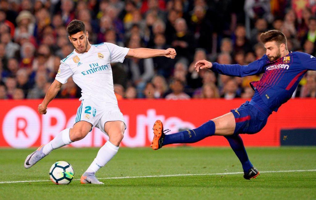 Gelandang Real Madrid Marco Asensio saat berduel dengan bek Barcelona Gerard Pique musim lalu (Foto: AFP/Josep Lago)