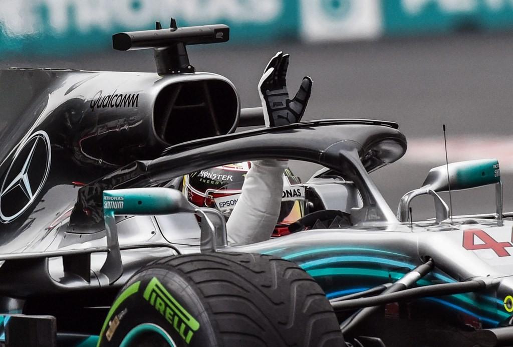 Lewis Hamilton menyapa para penggemar ketika masih berada di dalam jet darat Mercedes. (RODRIGO ARANGUA / AFP)
