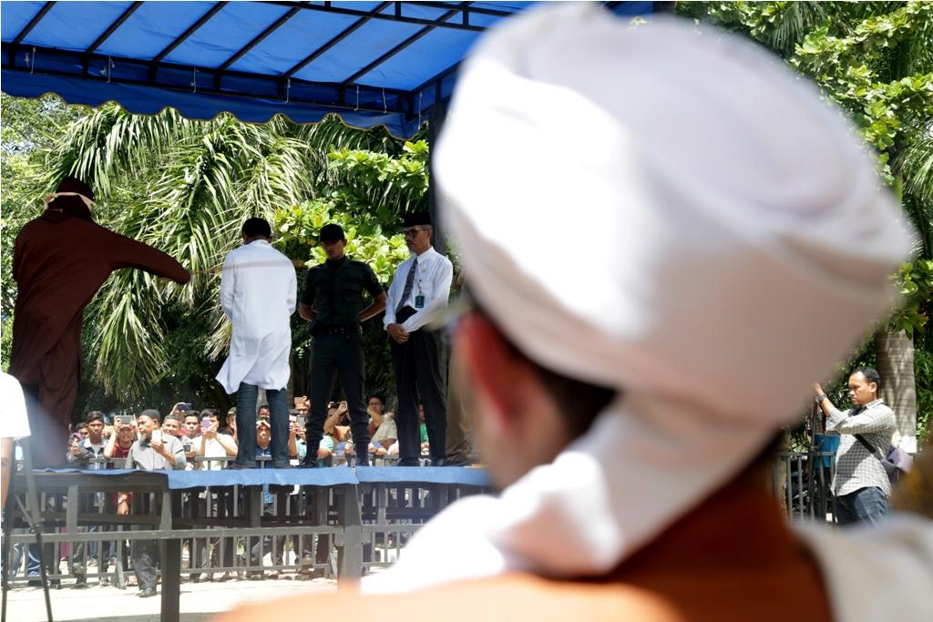Algojo (kiri) melaksanakan eksekusi hukum cambuk terhadap terpidana (dua kiri) pelanggar peraturan daerah (qanun) tentang Syariat Islam di Banda Aceh, Aceh, Senin (29/10/2018). Mahkamah Syar'iah Kota Banda Aceh menjatuhkan hukuman sebanyak tiga hingga 30