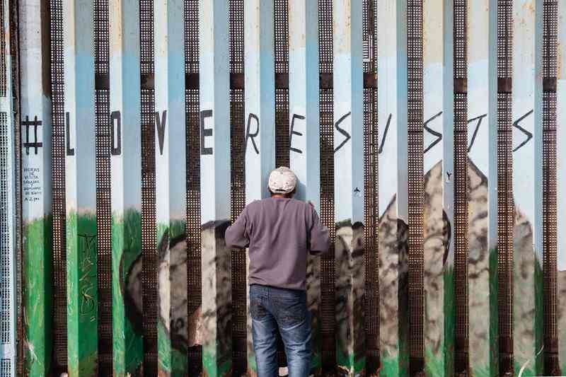 Seorang pria mengintip di tembok perbatasan yang memisahkan Amerika Serikat (AS) dan Meksiki. (Foto: AFP).