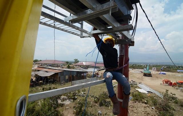 Pekerja memasang travo untuk mengalirkan listrik ke hunian sementara bagi korban gempa di Petobo, Palu, Minggu (28/10/2018). Antara Foto/Basri Marzuki