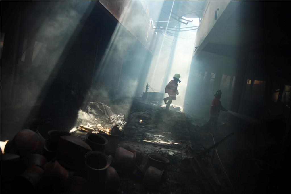 Petugas melakukan proses pendinginan pada bangunan yang terbakar di Pasar Legi, Solo, Jawa Tengah, Selasa (30/10/2018).