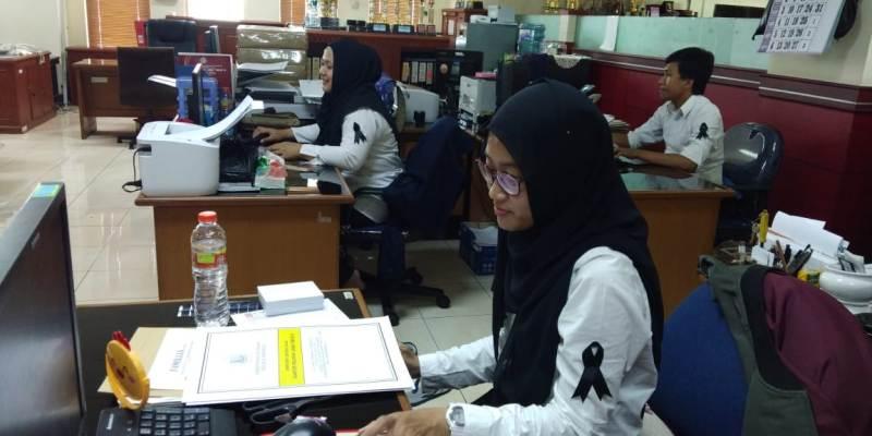 Pegawai Direktorat Jenderal Pajak (DJP) Jawa Timur III mengenakan pita berwarna hitam di lengan kiri.