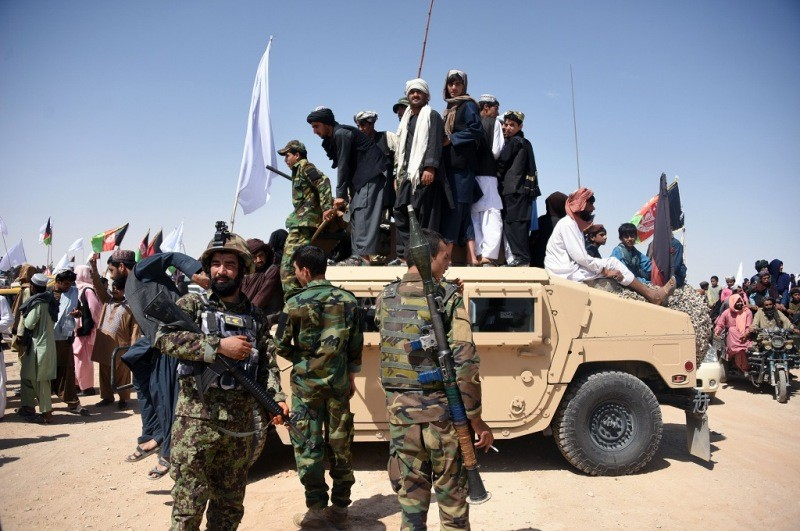 Militan Taliban beserta warga sipil dan pasukan pemerintah berada di Kandahar, Afghanistan, 17 Juni 2018, dalam merayakan gencatan senjata. (Foto: AFP/JAVED TANVEER).