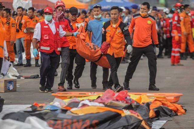 Petugas membawa kantong jenazah korban pesawat Lion Air JT 610. Foto: Antara/Muhammad Adimaja.
