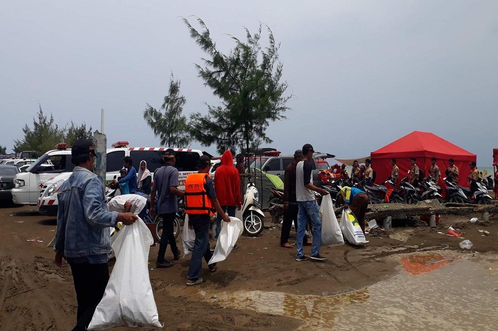 Petugas memunguti sampah di Pantai Tanjungpakis saat petugas tengah mencari korban dan pesawat Lion Air jatuh di perairan Tanjung, Karawang, Jumat, 2 November 2018, MI - Cikwan Suwandi