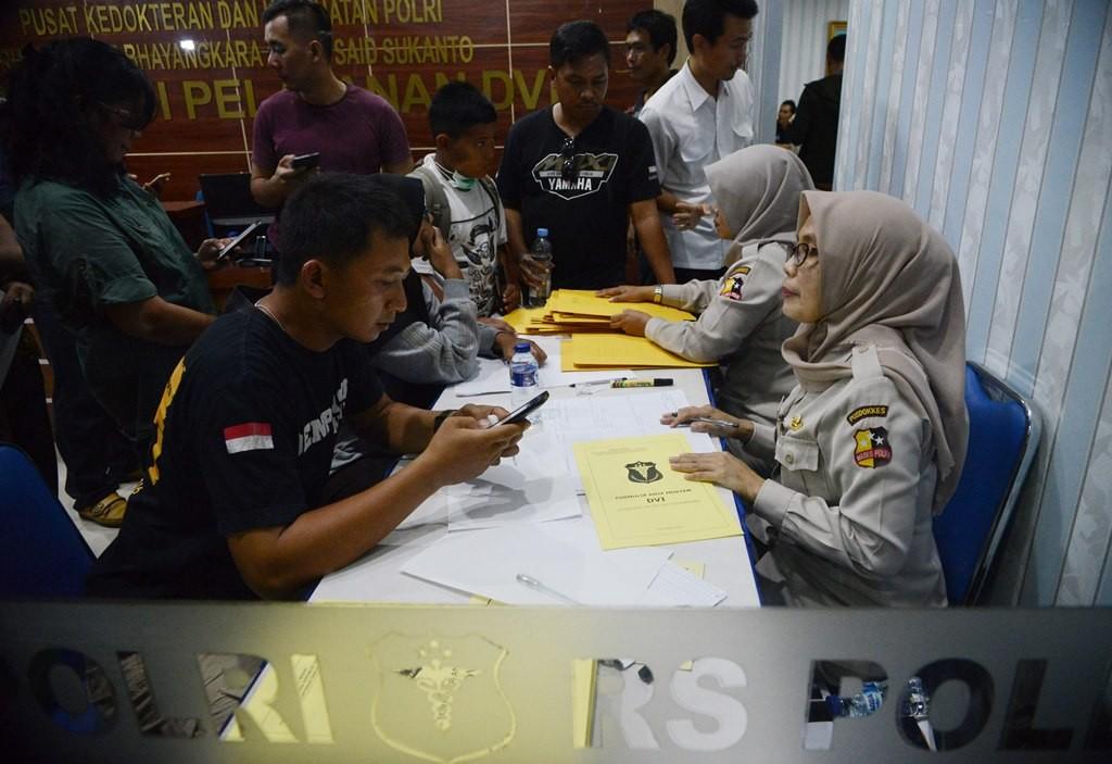 Petugas Posko DVI RS Polri melayan keluarga korban pesawat Lion Air JT610 yang datang untuk menyerahkan berkas milik korban di RS Polri. MI/M Irfan.