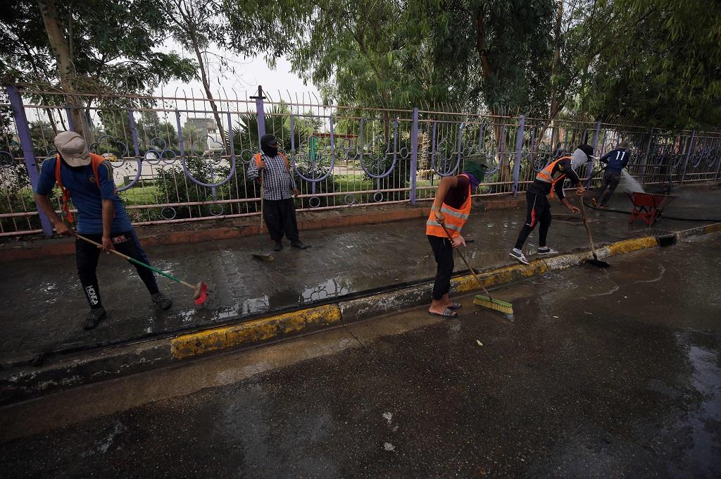 Petugas membersihkan lokasi bom bunuh diri di salah satu distrik Syiah di Baghdad, Irak, 24 Mei 2018. (Foto: AFP/AHMAD AL-RUBAYE)