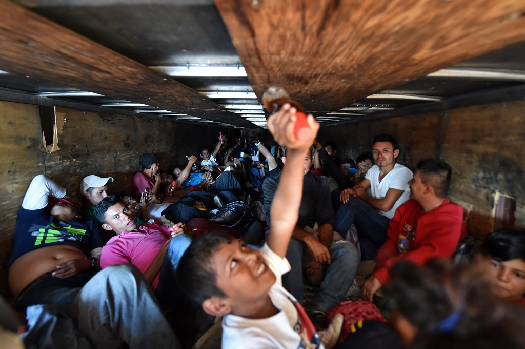 Sekelompok imigran asal Amerika Tengah menaiki sebuah truk menuju Mexico City, Meksiko, 5 November 2018, dalam upaya mencapai tujuan akhir ke AS. (Foto: AFP/RODRIGO ARANGUA)