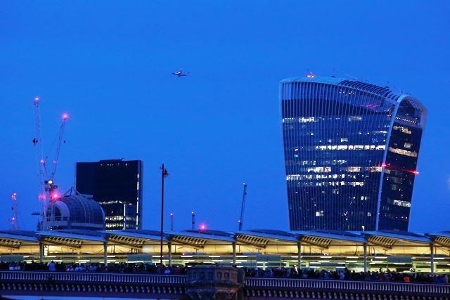 Walkie Talkie menjadi latar jembatan Blackfriars yang melintasi Sungai Thames. Gedung dengan desain unik di pusat bisnis London ini milik Lee Kum Kee Group yang berpusat di Hong Kong. AFP Photo/Justin Tallis