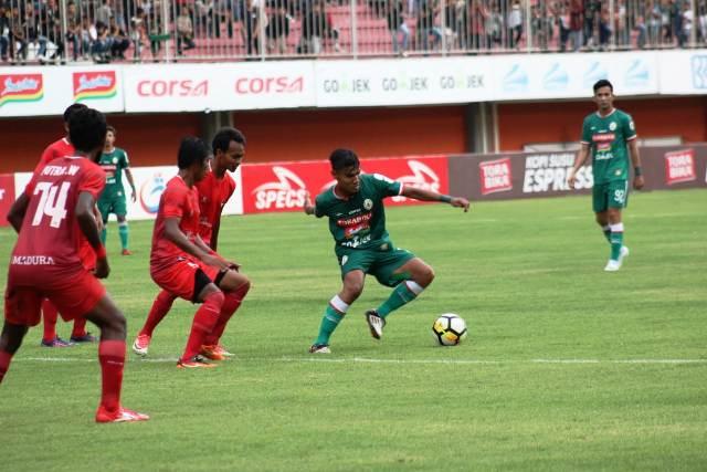 Pemain PSS, Ichsan Pratama membawa bola dijaga empat pemain Madura FC. Medcom.ID-Ahmad Mustaqim
