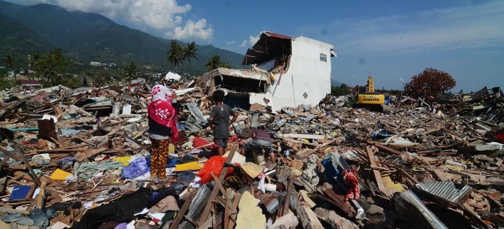 Seorang ibu bersama anaknya menyaksikan sisa-sisa reruntuhan rumahnya yang akan diratakan dengan tanah di area bekas likuifaksi di Kelurahan Balaroa, Palu, Sulawesi Tengah, Rabu (24/10/2018). ANTARA FOTO/Basri Marzuki.