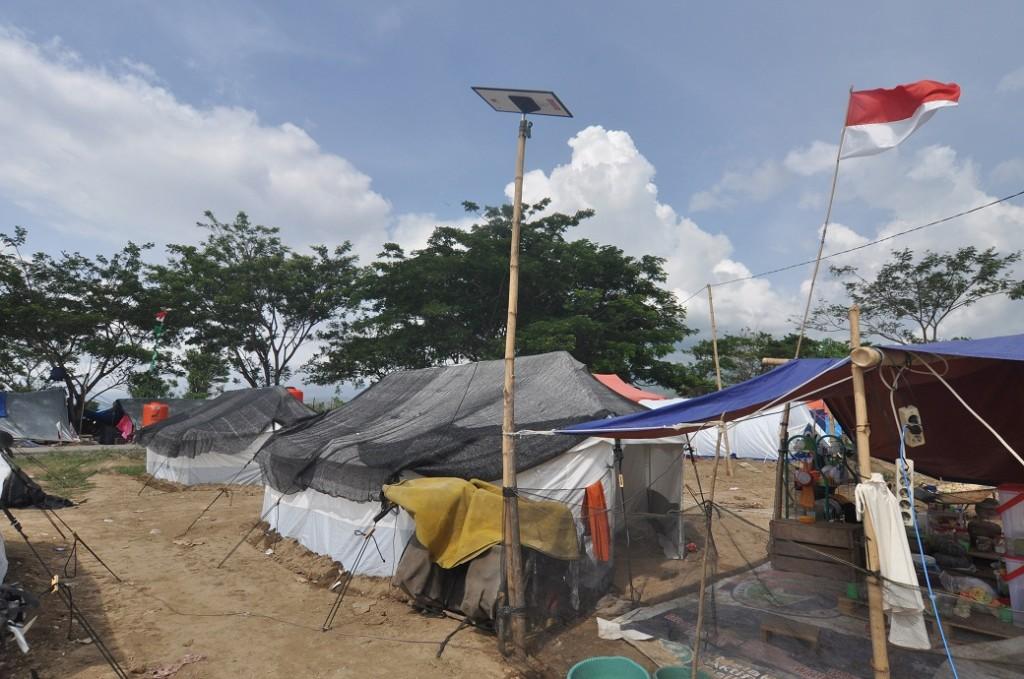 Panel listrik tenaga surya terpasang di salah satu tenda pengungsian korban gempa di Desa Lolu, Kabupaten Sigi, Sulawesi Tengah, Minggu (4/11/2018). ANTARA FOTO/Mohamad Hamzah.