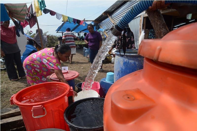 Relawan mengisi wadah dengan air bersih di kamp terpadu pengungsian korban likuifaksi Petobo, Palu, Sulawesi Tengah, Jumat (19/10/2018). ANTARA FOTO/Basri Marzuki.