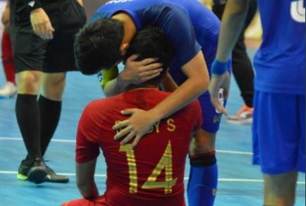 Pemain Thailand memberikan semangat kepada salah satu penggawa
