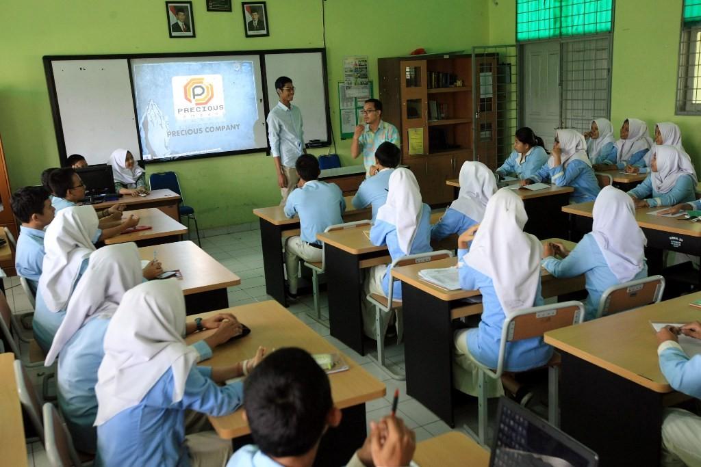 Guru sedang mengajar di depan kelas, MI/Panca Syurkani.
