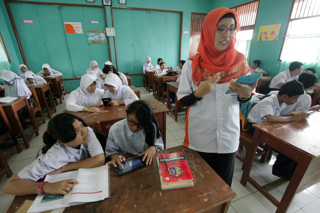 Seorang guru sedang mengajar di dalam kelas, MI/Bary Fathahilah.