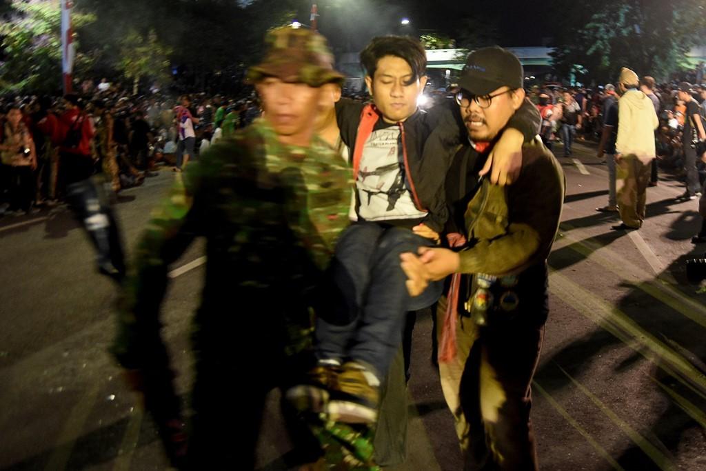 Sejumlah warga mengevakuasi korban yang terjatuh dari viaduk ketika menonton drama kolosal Surabaya Membara di Jalan Pahlawan Surabaya, Jawa Timur. (Foto: ANTARA/ M Risyal Hidayat)