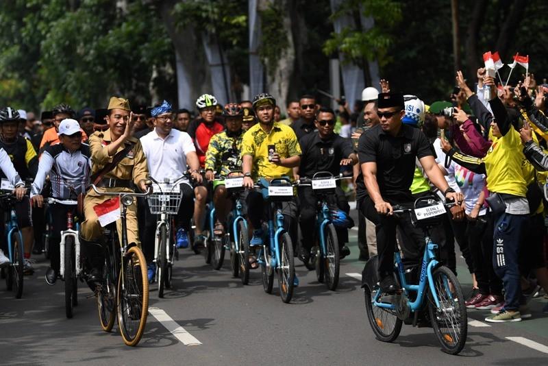 Presiden Joko Widodo (kedua kiri) didampingi Kepala Staf Presiden Moeldoko (kiri) dan Gubernur Jawa Barat Ridwan Kamil (ketiga kiri) menyapa warga ketika mengikuti kegiatan sepeda bersama dengan tema Bandung Lautan Sepeda di Bandung, Jawa Barat, Sabtu (10