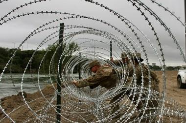 Prajurit AS memasang kawat berduri di sepanjang wilayah yang
