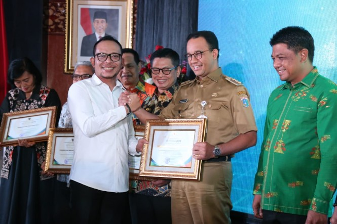 Menaker Hanif Dhakiri (kiri) memberikan penghargaan kepada Gubernur DKI Jakarta Anies Baswedan. (Foto: Dok. Kemenaker)