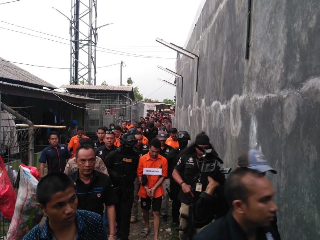 Tersangka Pembunuhan satu Keluarga di Bekasi, Jawa Barat, Haris Simamora digiring menuju kontrakannya. Foto: Istimewa.