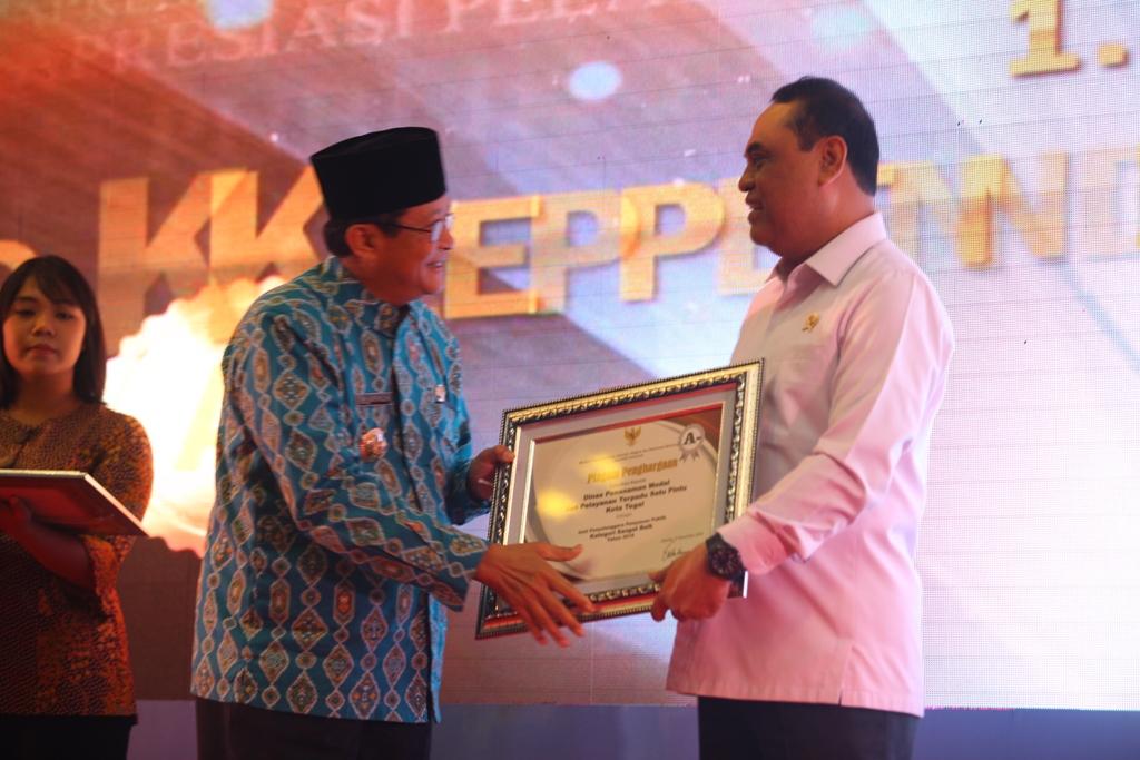 Menteri Pendayagunaan Aparatur Negara dan Reformasi Birokrasi Republik Indonesia, Syafrudin, memberikan penghargaan kepada walikota Tegal, M Nursholeh. (Medcom.id/Kuntoro Tayubi)